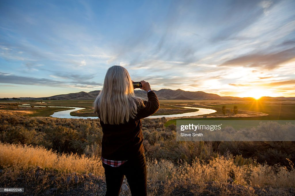 Caucasian woman photographing sunset over winding river : Stock Photo