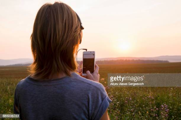 Caucasian woman photographing sunset with cell phone