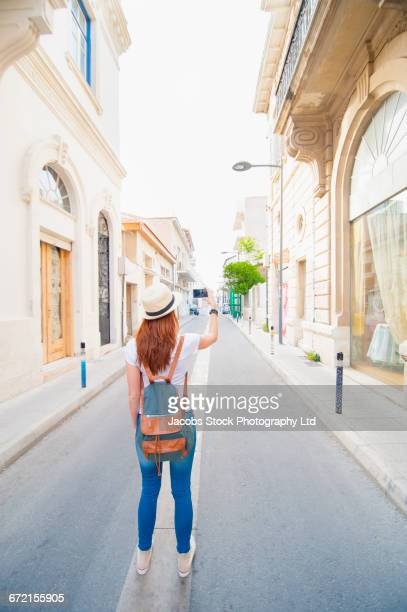Caucasian woman photographing with cell phone in street
