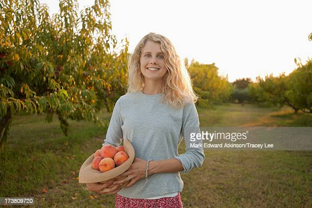 Caucasian woman picking fruit in orchard