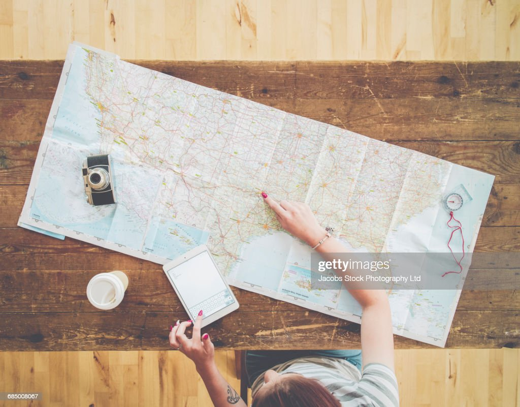 Caucasian woman planning trip with digital tablet and map on wooden table : Foto de stock