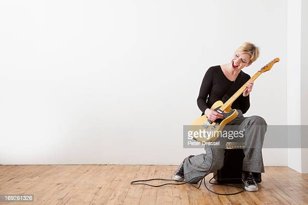Caucasian woman playing electric guitar