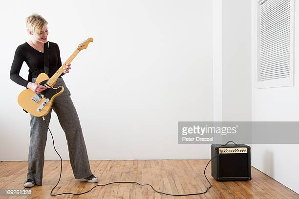 Caucasian woman playing electric guitar