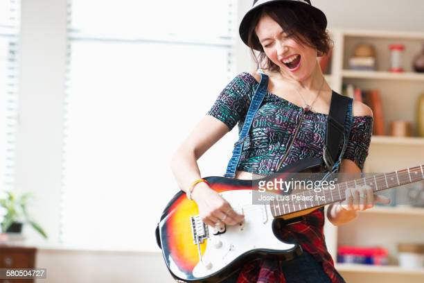Caucasian woman playing guitar in living room