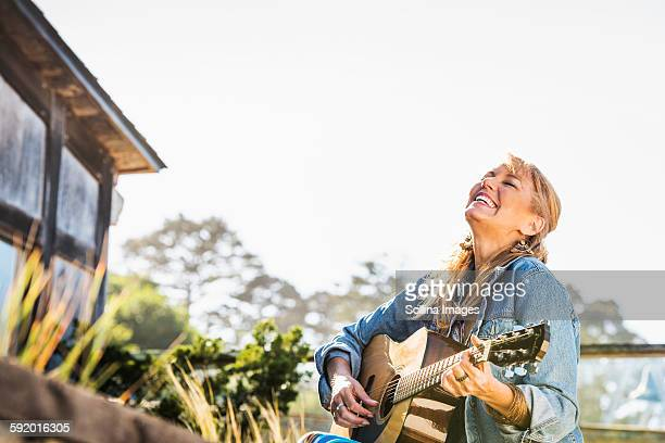 Caucasian woman playing guitar on porch