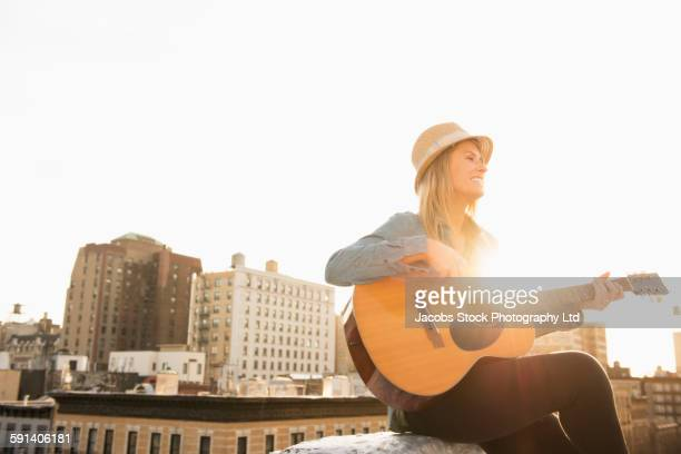 Caucasian woman playing guitar on urban rooftop