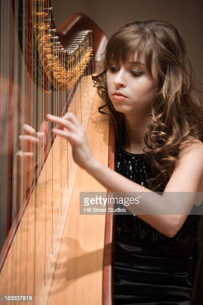 Caucasian woman playing harp