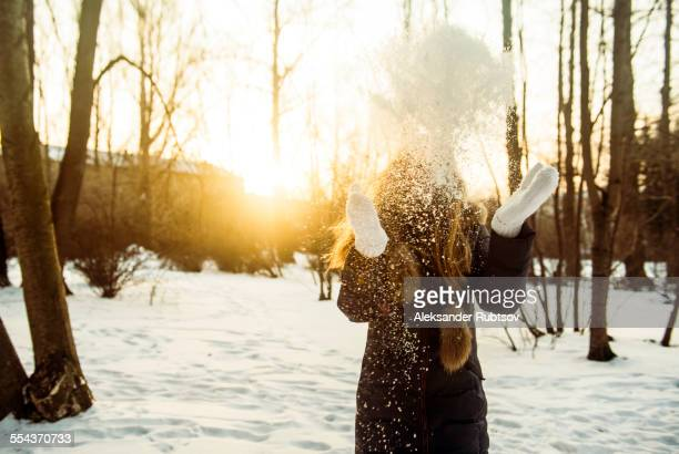 Caucasian woman playing in snowy field