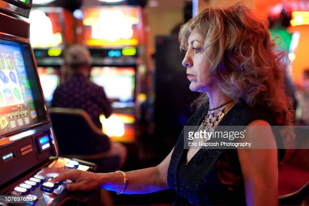 caucasian woman playing slot machine in casino - gambling addiction stock pictures, royalty-free photos & images
