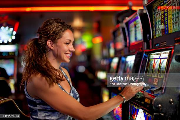 caucasian woman playing slot machine in casino - casino stock pictures, royalty-free photos & images