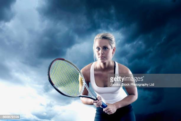 Caucasian woman playing tennis under cloudy sky