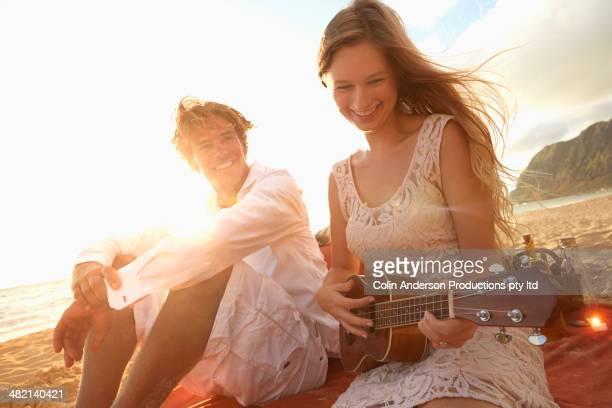 Caucasian woman playing ukulele for boyfriend on beach