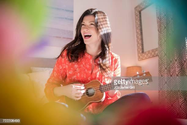 caucasian woman playing ukulele - ukulele stock pictures, royalty-free photos & images