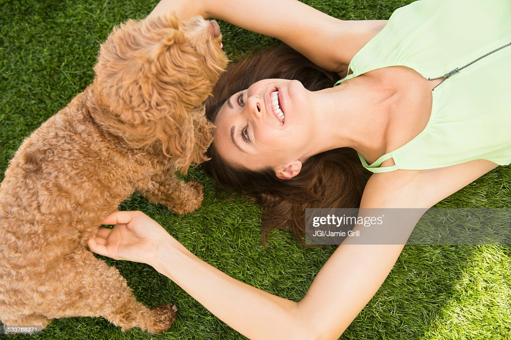 Caucasian woman playing with dog on lawn : Stock Photo