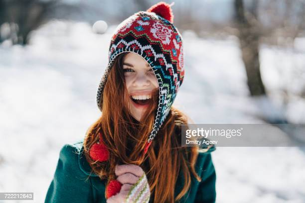 Caucasian woman playing with hat in winter