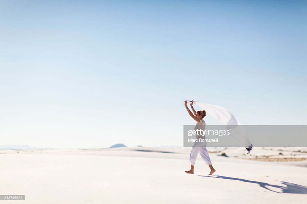 Caucasian woman playing with scarf on sand dune : Foto stock