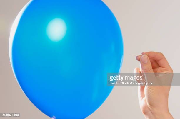 caucasian woman popping blue balloon with pin - stecknadel stock-fotos und bilder