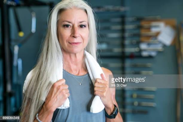 Caucasian woman posing in gymnasium wearing towel