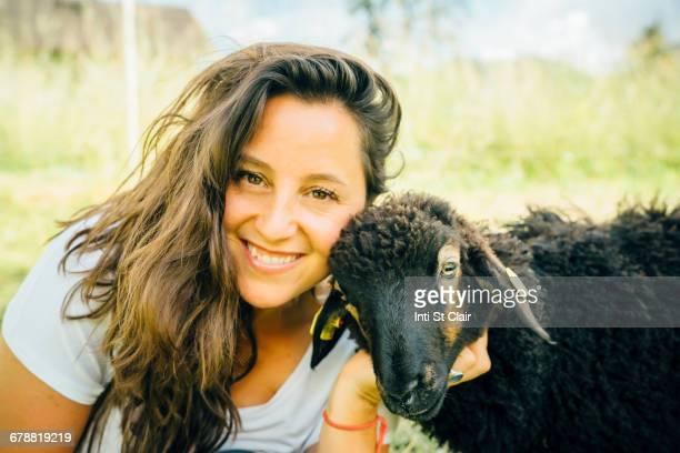 Caucasian woman posing with sheep