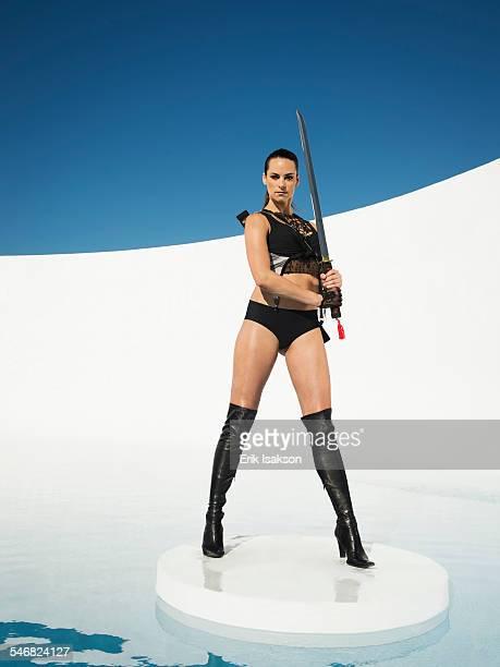 Caucasian woman posing with sword on ice floe
