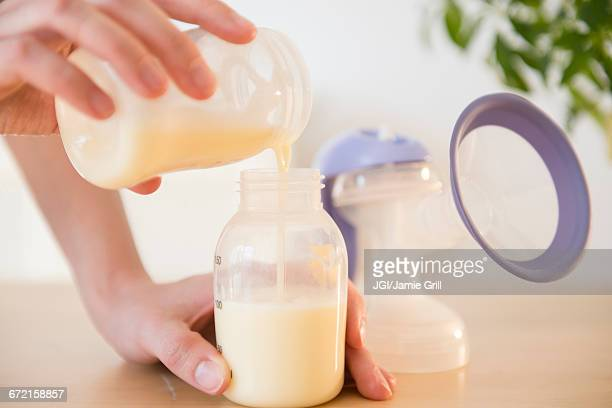 Caucasian woman pouring breast milk into bottle