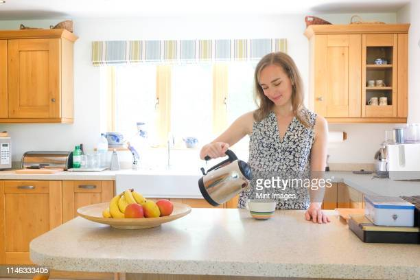 caucasian woman pouring coffee from pot in kitchen - gratitude stock pictures, royalty-free photos & images