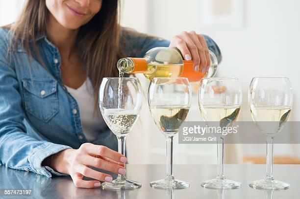 Caucasian woman pouring glasses of white wine
