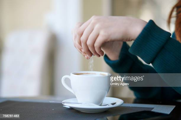 caucasian woman pouring sugar into coffee - sugar coffee stock photos and pictures