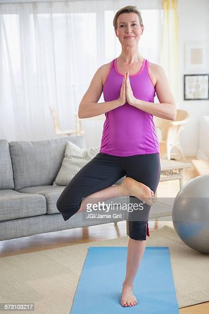 Caucasian woman practicing yoga in living room