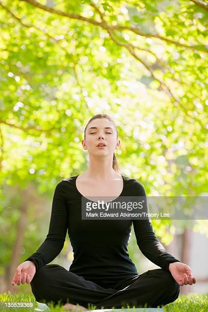 caucasian woman practicing yoga in park - lotuspositie stockfoto's en -beelden