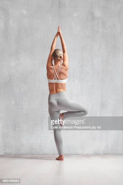 caucasian woman practicing yoga in studio - tree position stock photos and pictures