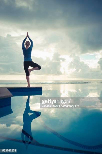 Caucasian woman practicing yoga near swimming pool