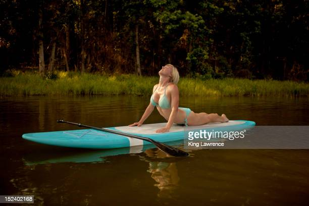 caucasian woman practicing yoga on paddleboard - tennessee v arkansas stock pictures, royalty-free photos & images
