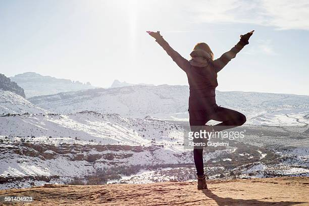 caucasian woman practicing yoga on remote hilltop - tree position stock photos and pictures