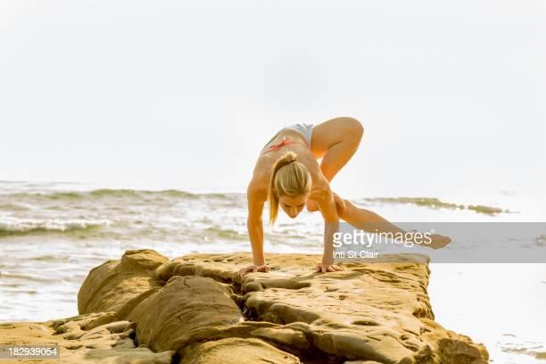 Caucasian woman practicing yoga on rocky beach