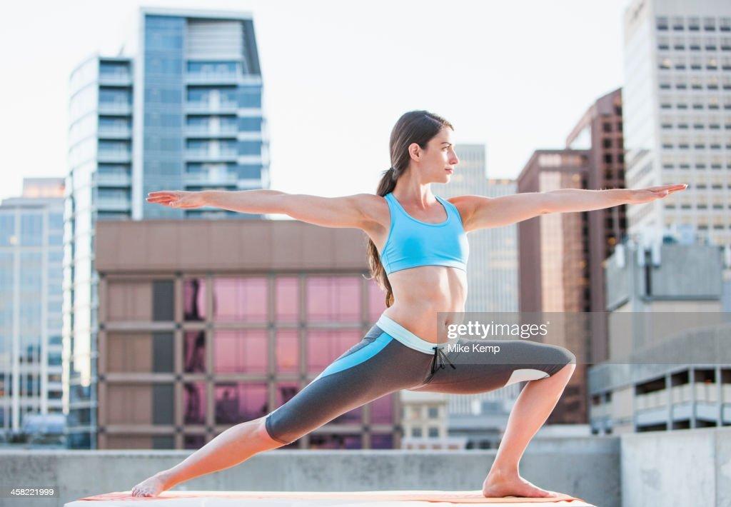 Caucasian woman practicing yoga on urban rooftop : Stock Photo