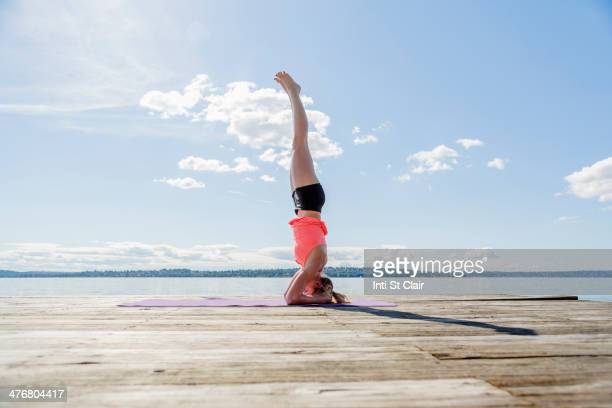Caucasian woman practicing yoga on wooden dock