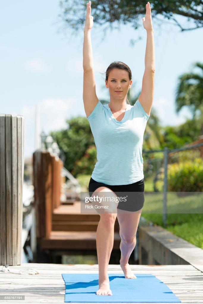 Caucasian woman practicing yoga on wooden dock : Foto stock
