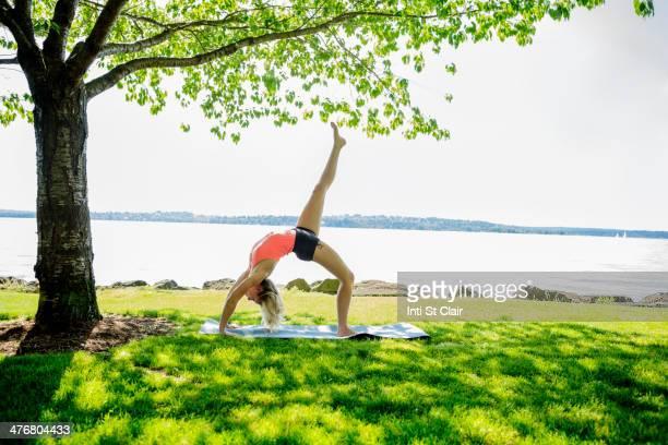 Caucasian woman practicing yoga outdoors