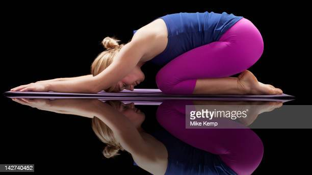 caucasian woman practicing yoga - childs pose stock photos and pictures