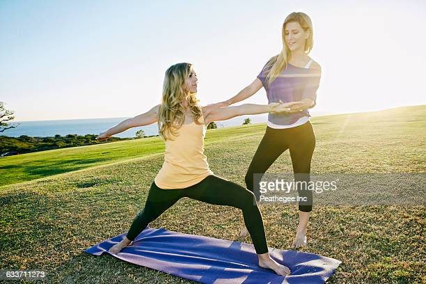 Caucasian woman practicing yoga with trainer in field