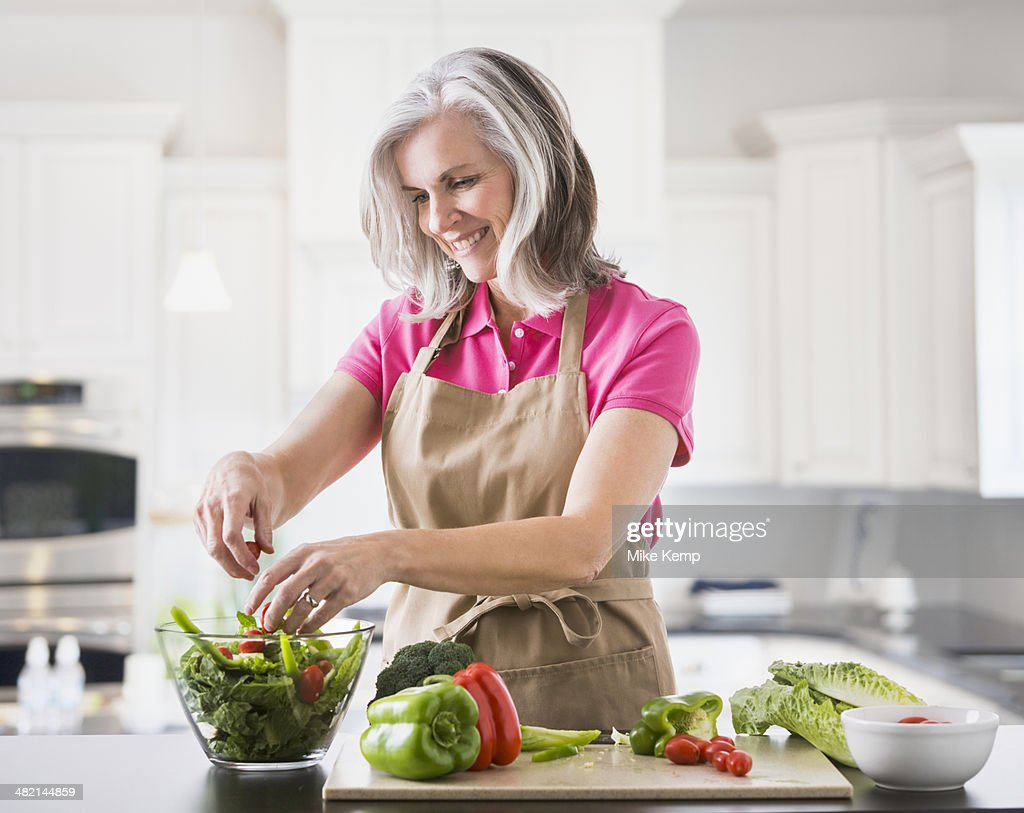 Caucasian woman preparing salad in kitchen : Stock Photo