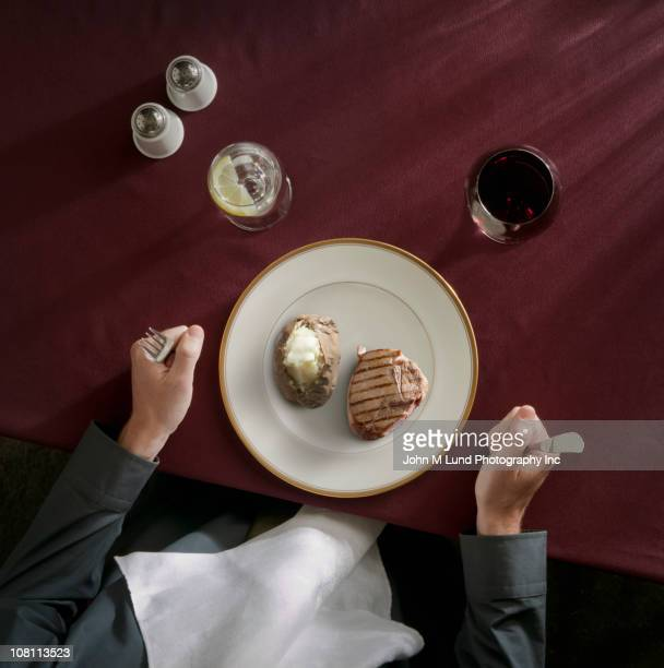 Caucasian woman preparing to eat meat and potatoes