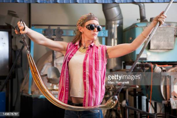 Caucasian woman pulling glass in glass blowing studio