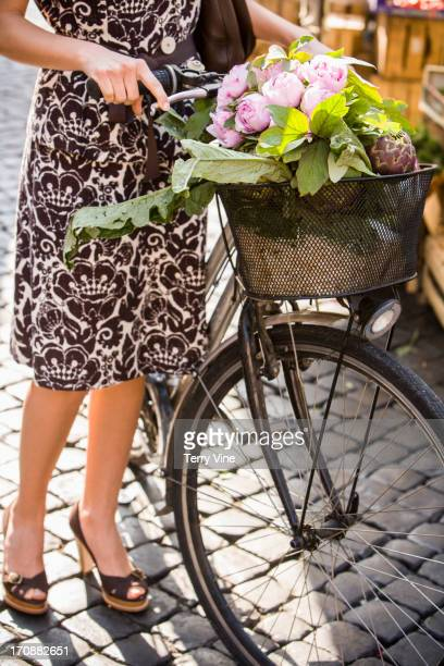 Caucasian woman pushing bicycle with flowers