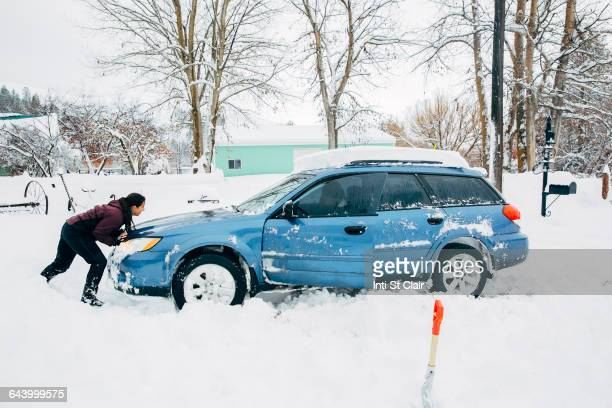 Caucasian woman pushing car stuck in snow