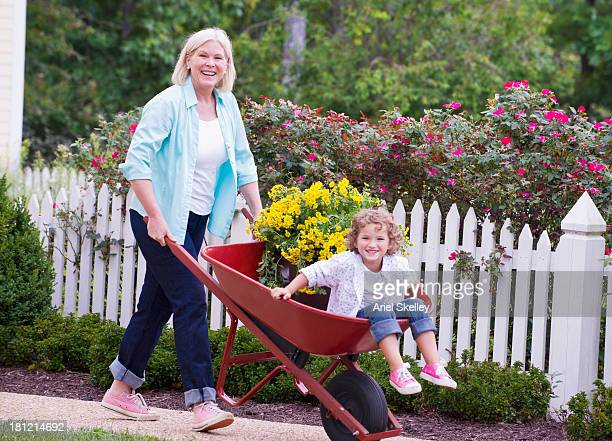 caucasian woman pushing granddaughter in wheelbarrow - picket stock pictures, royalty-free photos & images