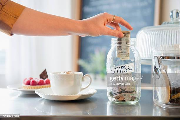 Caucasian woman putting money in tip jar
