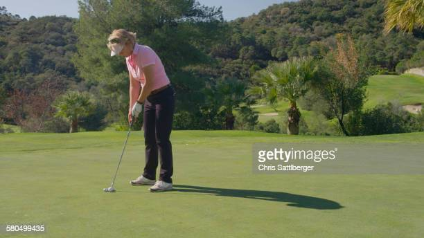 caucasian woman putting on golf course - putting stock pictures, royalty-free photos & images