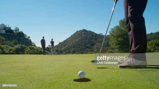 Caucasian woman putting on golf course